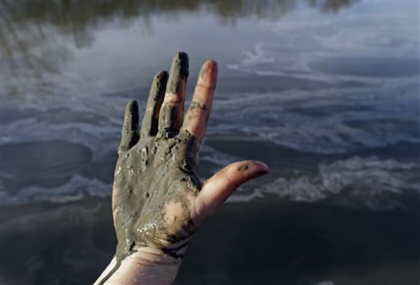 Amy Adams, North Carolina campaign coordinator with Appalachian Voices, shows her hand covered with wet coal ash from the Dan River.