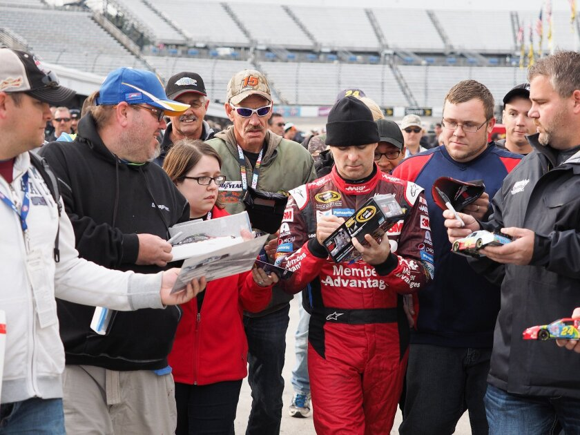 NASCAR Sprint Cup driver Jeff Gordon signs autographs before practice for Sunday's NASCAR Sprint Cup auto race at Martinsville Speedway in Martinsville, Va., on Saturday, Oct. 31, 2015. (AP Photo/Steve Sheppard)