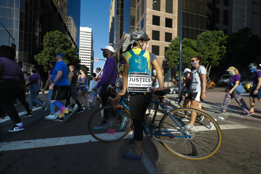 """A bicyclist with a """"Justice for Breonna Taylor"""" sign participates in a 5K event"""