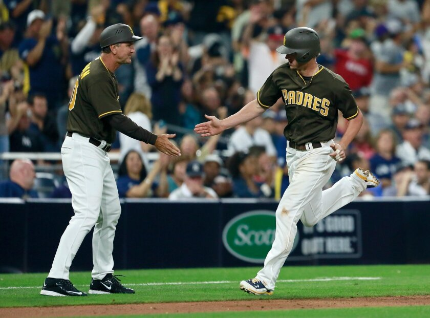 San Diego Padres Wil Myers celebrates with third base coach Glenn Hoffman after hitting a home run against the New York Yankees.