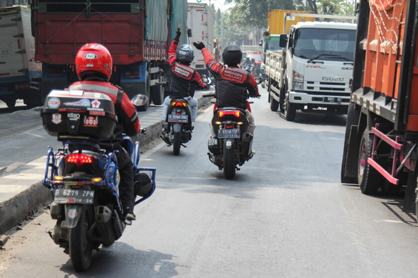 Three motorcycles travel down a street.