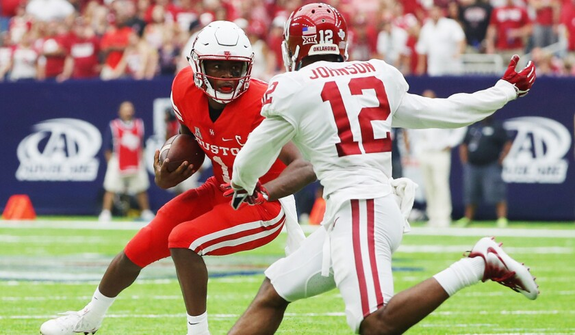 Houston's Greg Ward Jr., left, scrambles and Oklahoma's Will Johnson gives chase during the Cougars' win Saturday.