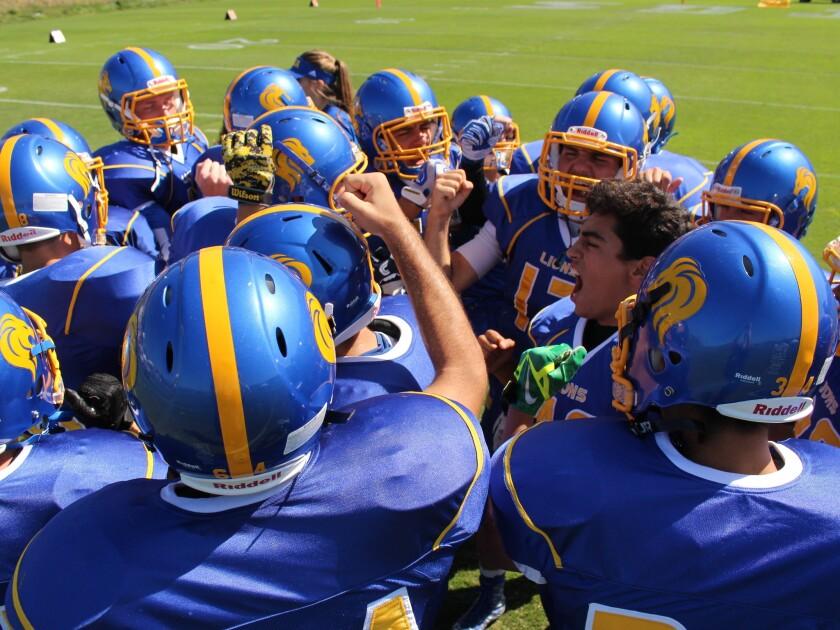 SDJA football team players cheer each other on.