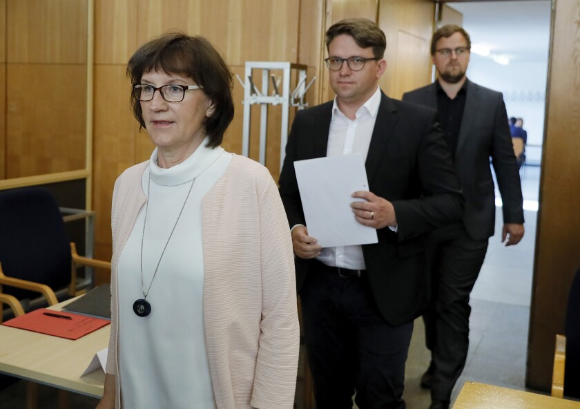 Walter Luebcke's widow Irmgard Braun-Luebcke, left and her sons Jan-Hendrick Luebcke and Christoph Luebcke in the courtroom for the continuation of the trial in Frankfurt, Germany, Thursday, July 2, 2020. A far-right extremist in Germany was convicted Thursday, Jan. 28, 2021 and sentenced to life in prison for the murder of a regional politician who had advocated helping refugees — a brazen killing that shocked the country. Prosecutors, defendants and co-plaintiffs have lodged appeals against the verdict. (Ronald Wittek/Pool Photo via AP)
