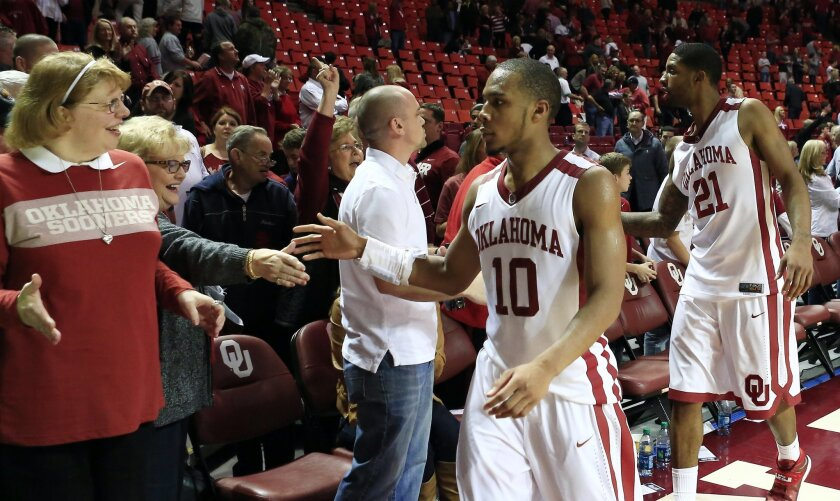 Oklahoma guard Jordan Woodard (10) and Cameron Clark (21) celebrate with fans following a win against Iowa State in an NCAA college basketball game in Norman, Okla., on Saturday, Jan. 11, 2014. Oklahoma won 87-82. (AP Photo/Alonzo Adams)