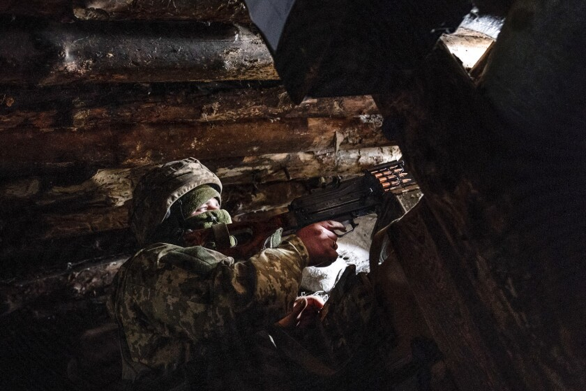 FILE - In this March 5, 2021, file photo, a Ukrainian serviceman keeps ready a machine gun in his shelter near the front-line town of Krasnohorivka, eastern Ukraine. Tensions are rising over the conflict in eastern Ukraine, with growing violations of a cease-fire and a massive Russian military buildup near its border with the region. (AP Photo/Evgeniy Maloletka, File)