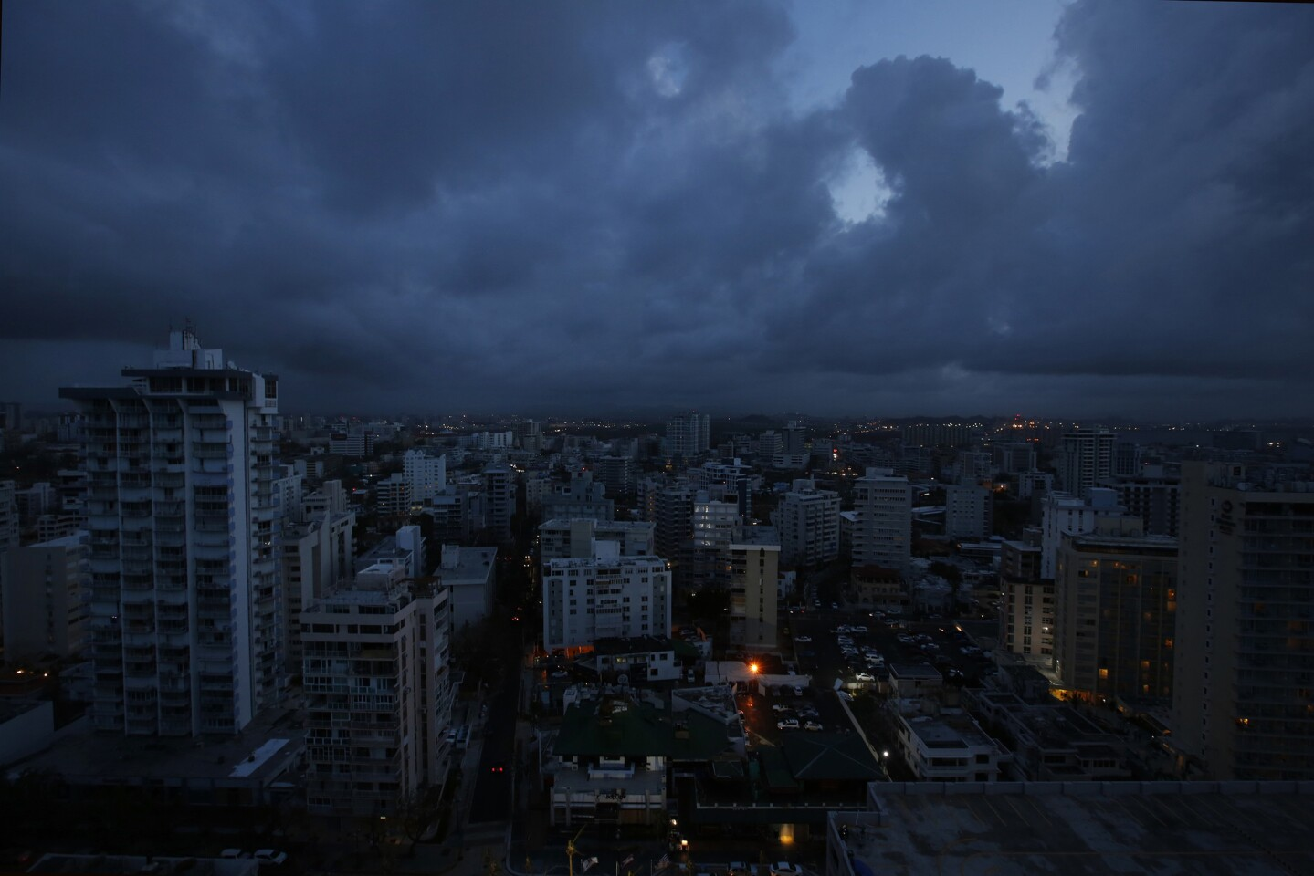 Darkness falls on downtown San Juan which remains without power. Puerto Rico officials say it will likely be four to six months before power is fully restored across the U.S. territory of 3.5 million people.