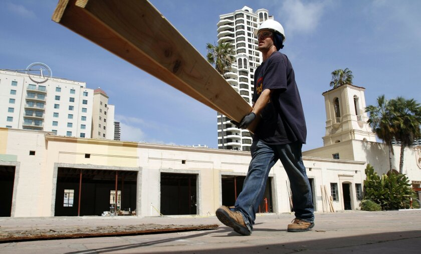 Construction worker Christopher Pattbrese carries lumber across the entrance plaza of the old San Diego Police headquarters that is being renovated into an approximately 100,000-square-foot retail, dining and entertainment destination in the Seaport District.