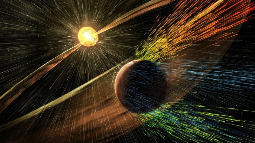 This image made available by NASA on Thursday, Nov. 5, 2015 shows an artist's rendering of a solar storm hitting the planet Mars and stripping ions from the planet's upper atmosphere. NASA's Mars-orbiting Maven spacecraft has discovered that the sun robbed the red planet of its once-thick atmospher