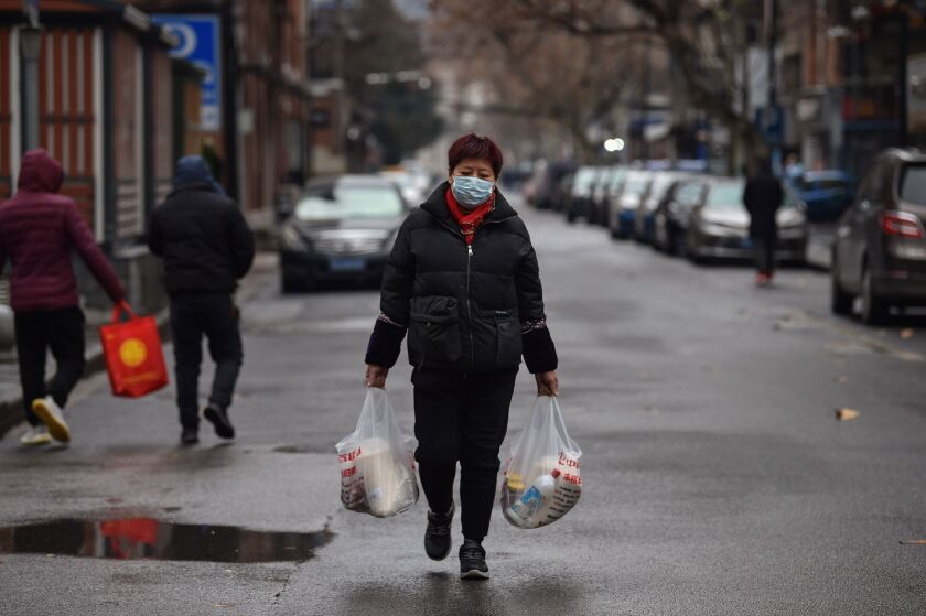 Woman wearing face mask walks home from a grocery shopping trip in Wuhan, China