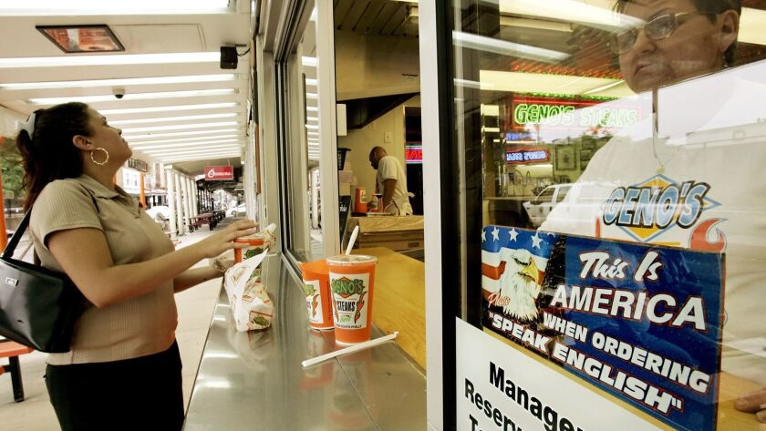 Angelica Marquez, left, collects her order as Cathy Merlino is seen behind a sign telling customers
