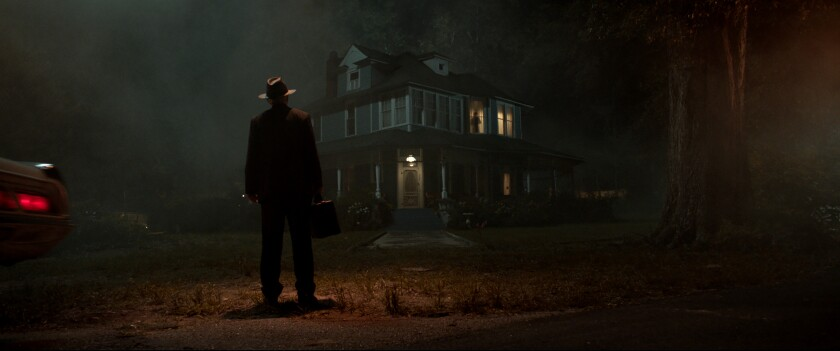 In the dark, a man in a fedora stands in front of a spooky-looking house.