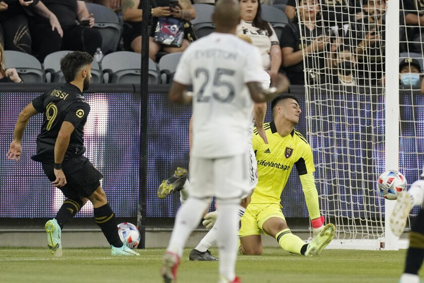 Los Angeles FC forward Diego Rossi, left, scores on Real Salt Lake goalkeeper David Ochoa, right, as midfielder Everton Luiz watches during the first half of a Major League Soccer match Saturday, July 17, 2021, in Los Angeles. (AP Photo/Mark J. Terrill)