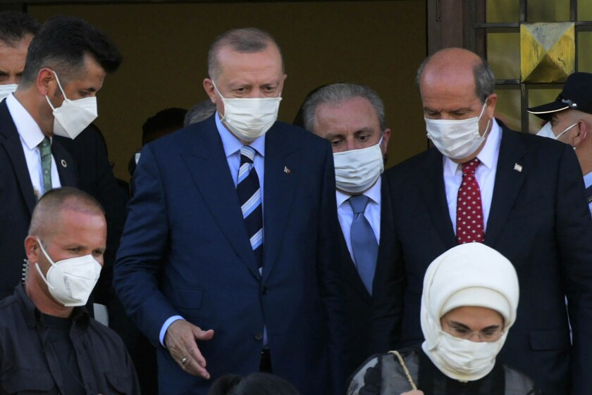 Turkish President Recep Tayyip Erdogan, center, and Turkish Cypriot leader Ersin Tatar, right, leave after their meeting in the Turkish occupied area at north part of divided capital Nicosia, Cyprus, on Monday, July 19, 2021. Speaking after Eid al-Adha prayers in northern Cyprus, President Recep Tayyip Erdogan said his country will talk with the Taliban regarding Turkey's bid to operate and secure the airport in the Afghan capital, Kabul. (AP Photo/Nedim Enginsoy)