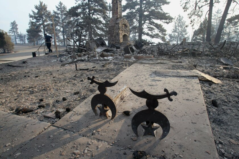 A fireplace and two andirons were all that  were left of the Shriner Camp lodge the day after the Chariot fire swept through