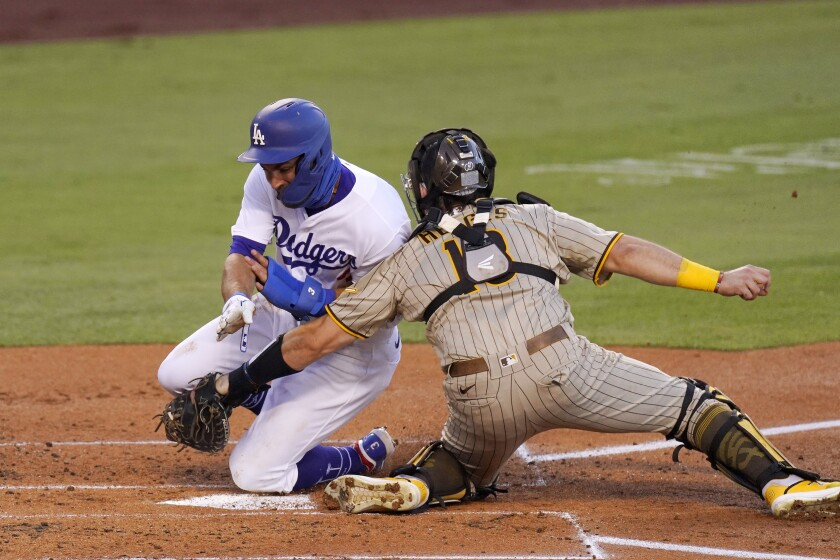 Dodgers' Chris Taylor collides with San Diego Padres catcher Austin Hedges as he is tagged out while trying to score.
