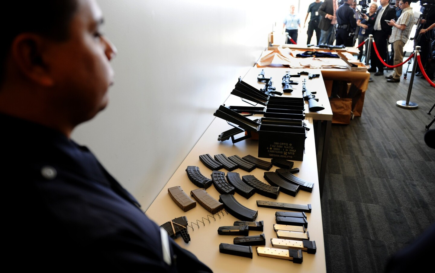 An officer stands by a cache of weapons that were found at the home of Daniel Yealu, the man accused of shooting one officer in the lobby of a police station.