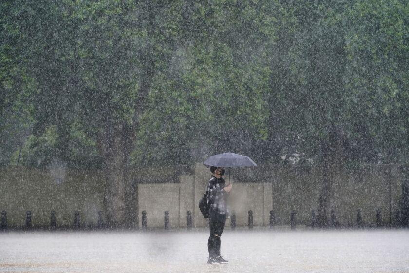Una mujer esta parada en medio de la lluvia en Horse Guards Parade en Londres el 25 de julio del 2021. (Victoria Jones/PA vía AP)