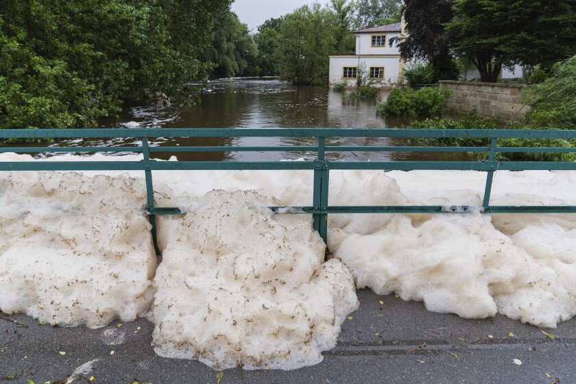 Foam washed up by the high water of the Aisch river has piled up at the bridge near the Lauf mill in Lauf, Germany, Wednesday, July 14, 2021. Storms caused widespread flooding across central Germany overnight, with authorities warning that more rain is on the way. (Nicolas Armer/dpa via AP)