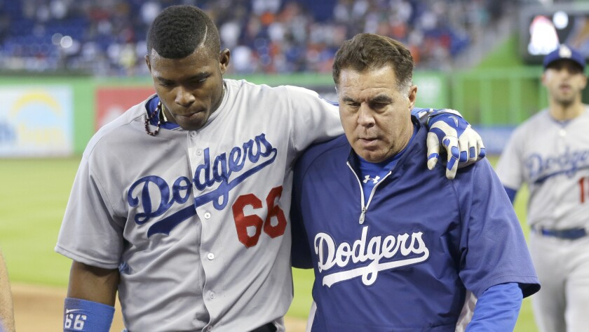 Dodgers right fielder Yasiel Puig, left, is helped off the field by a trainer after colliding with the outfield fence while chasing after a hit during the ninth inning of the team's 5-4 loss to the Miami Marlins on Sunday.