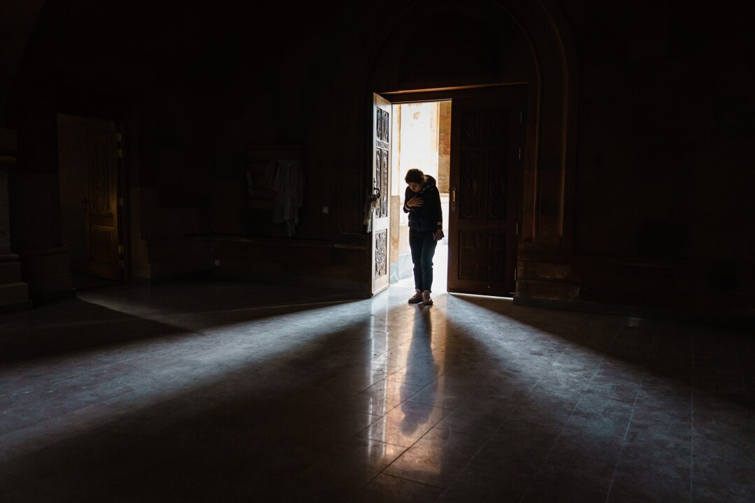 A woman bows her head in prayer before exiting the Holy Mother of God Cathedral.