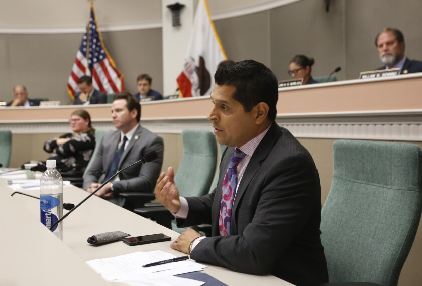 FILE - In this Aug. 12, 2019 file photo Assemblyman Miguel Santiago, D-Los Angeles, questions State Auditor Elaine Howle about an audit her office performed, during a hearing in Sacramento, Calif. Gov. Gavin Newsom signed a measure authored by Santiago that will let some adult children add their parents as dependents on their health insurance plans. The law would not apply to people who get health insurance through their work and only apply to people who purchase their own insurance on the individual market. (AP Photo/Rich Pedroncelli, File)