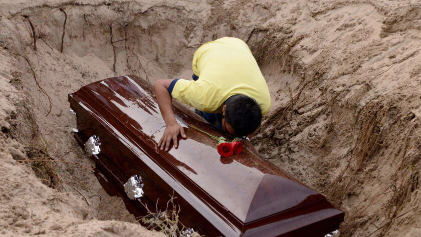A son of Mexican journalist Carlos Dominguez, killed on Jan. 13 in the state of Tamaulipas, mourns over his coffin during his funeral in Guerrero state. Dominguez was the first journalist killed in Mexico in 2018.