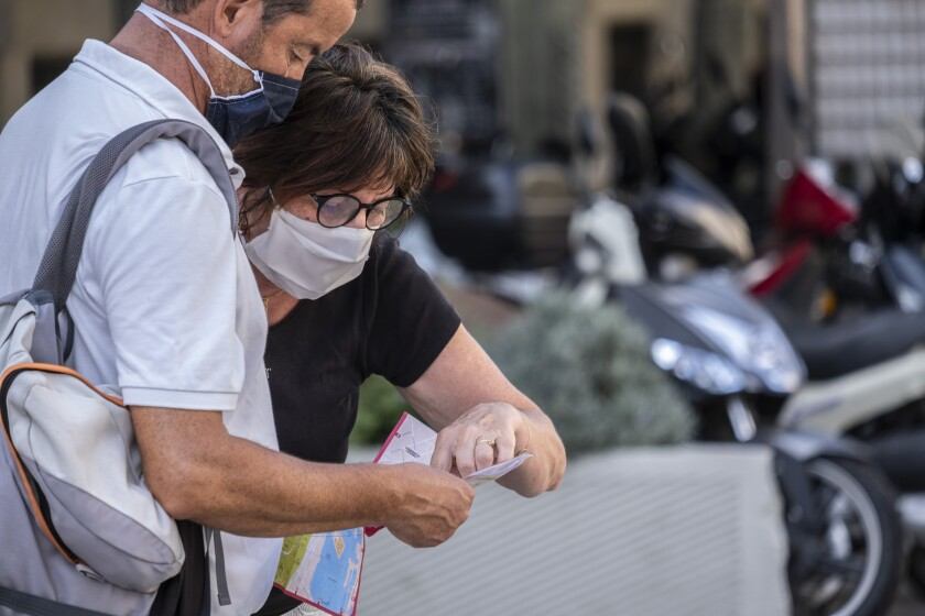 A tourist couple wearing facemasks consult a map of the city of Barcelona