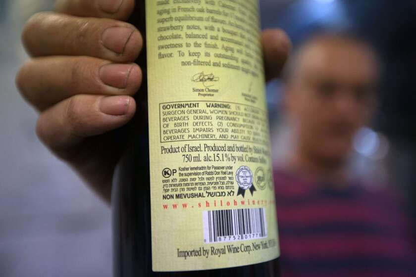 Amichai Luria presents a bottle of his wine, used mainly for export, at the Shilo winery in the Jewish settlement of Shilo in the West Bank on Nov. 12.