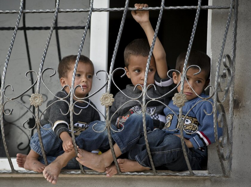 Kurdish children sit at a window in Suruc, on the Turkish side of the border with Syria, across from the Syrian town of Kobani, Monday, Oct. 27, 2014. Kobani, also known as Ayn Arab, and its surrounding areas, has been under assault by extremists of the Islamic State group since mid-September and i