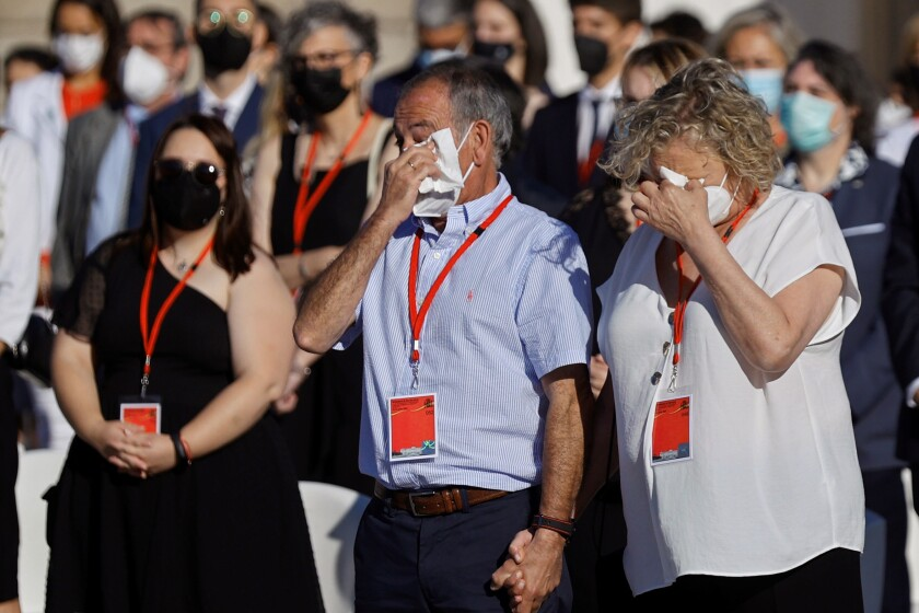 Participants cry during a ceremony to honour the victims of COVID-19 and the health worker at the Royal Palace in Madrid, Thursday, July 15, 2021. (Emilio Naranjo, Pool Photo via AP)