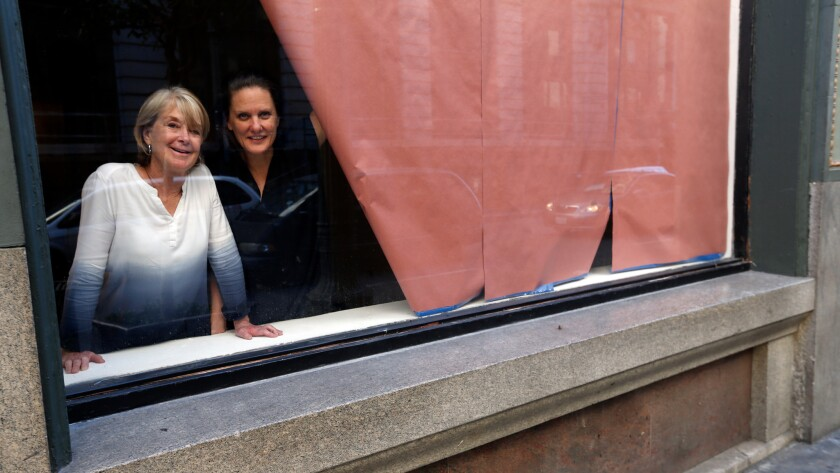 Artists Suzanne Lacy, left, and Andrea Bowers in the windows of the Main Museum in downtown L.A. in October.