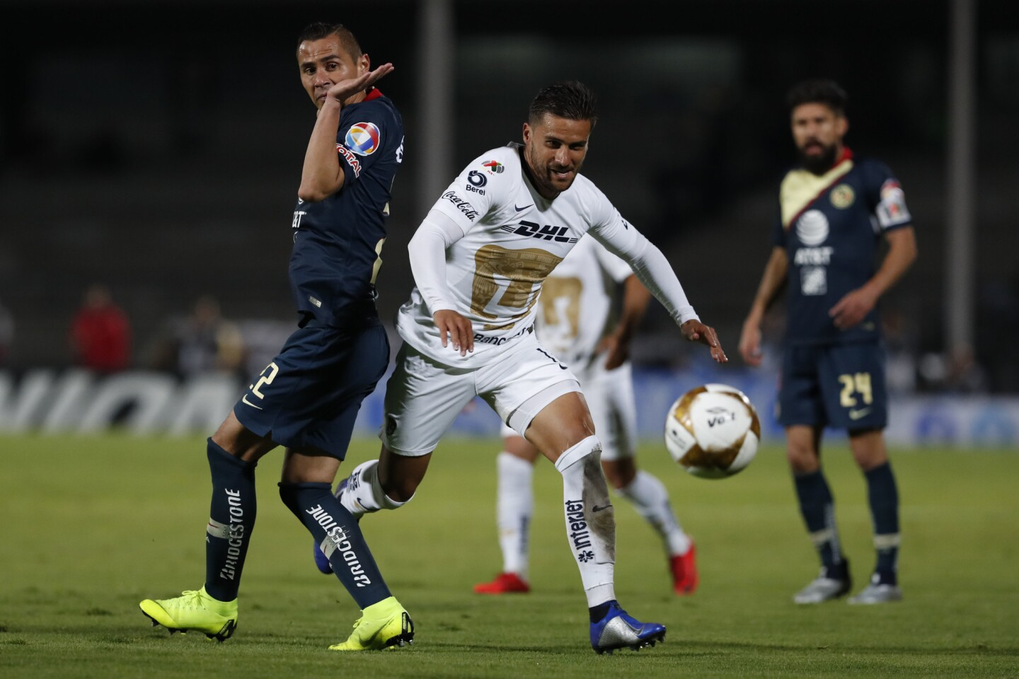 Pumas' Andres Iniestra, center, goes for the ball past America's Paul Aguilar during a Mexico soccer league first leg semifinals match in Mexico City, Thursday, Dec. 6, 2018. (AP Photo/Moises Castillo)