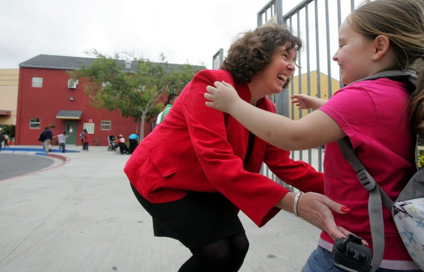 Cindy Marten, principal at Central Elementary School, greets student Kayla Moyer, 8, on Wednesday. Teachers at disadvantaged schools like this got a disproportionate number of pink slips warning of layoffs.