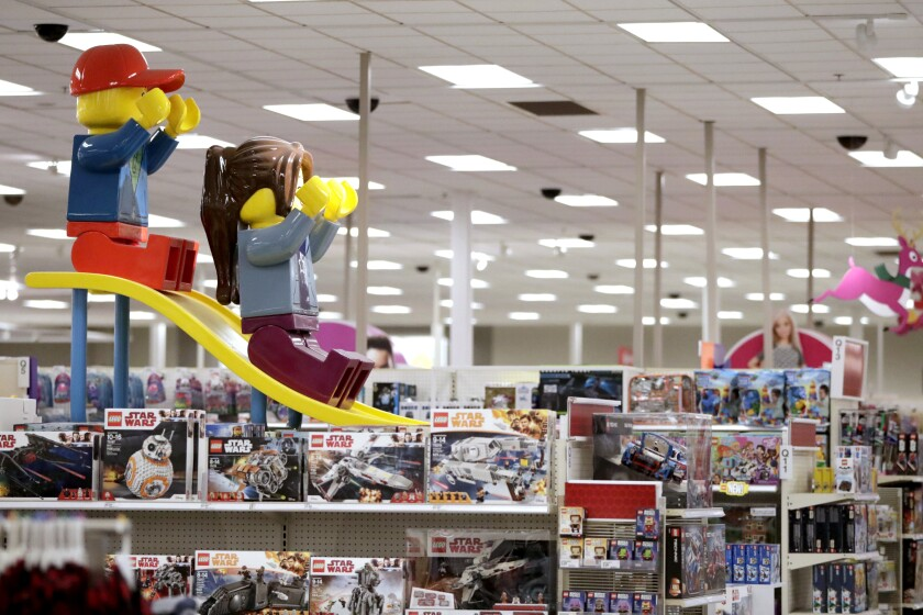 FILE- In this Friday, Nov. 16, 2018, file photo photo a display shows two large Lego toys on a slide near the toy section at a Target store in Bridgewater, N.J. The parent company of Toys R Us is turning to a rival to restart its e-commerce business ahead of the holiday shopping season. Tru Kids Brands is teaming up with discounter Target Corp. to relaunch Toysrus.com, according to a joint release. (AP Photo/Julio Cortez, File)
