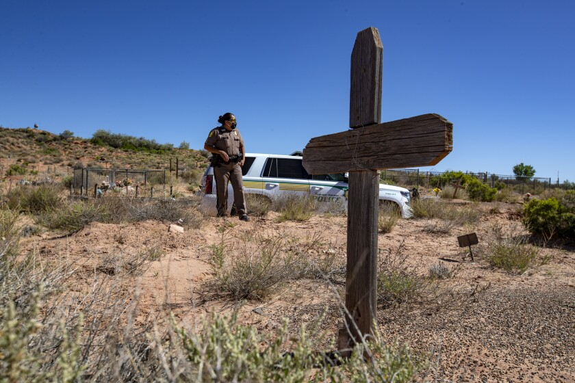 Navajo Nation Police Officer Carolyn Tallsalt looks out at dried sagebrush where her uncle was buried in April in Arizona.