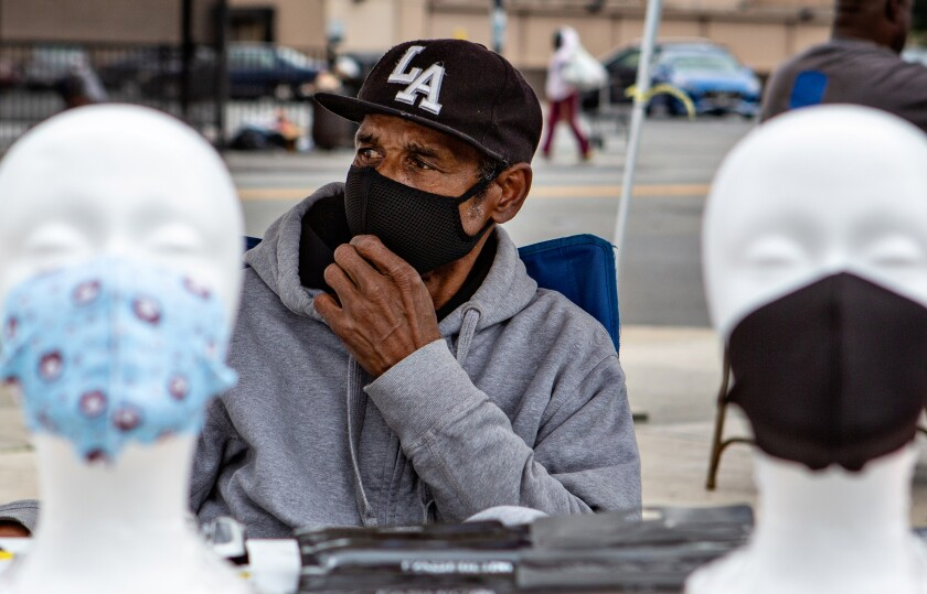 Larry Hickman of Los Angeles sells a variety of face mask on the corner of Western and Manchester Avenue in South Los Angeles