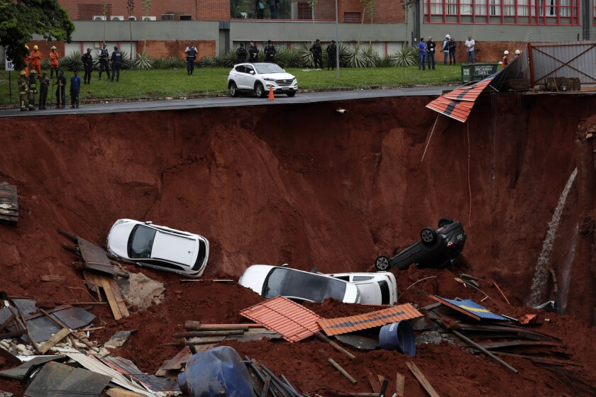 Vehicles lay at the bottom of a construction site after they fell in due to a collapse of a road next to it, caused by heavy rains in the center of Brasilia, Brazil, Tuesday, Dec. 10, 2019. There were no victims reported. (AP Photo/Eraldo Peres)