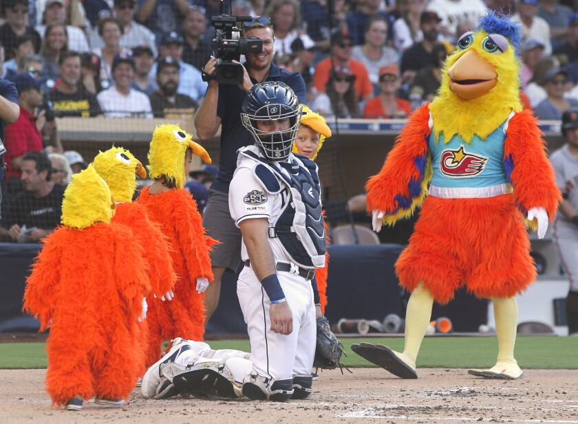 The San Diego Chicken, played by Ted Giannoulas, leads a group of children dressed as baby chicks past Padres catcher Austin Hedges during Saturday's game against the Giants at Petco Park.