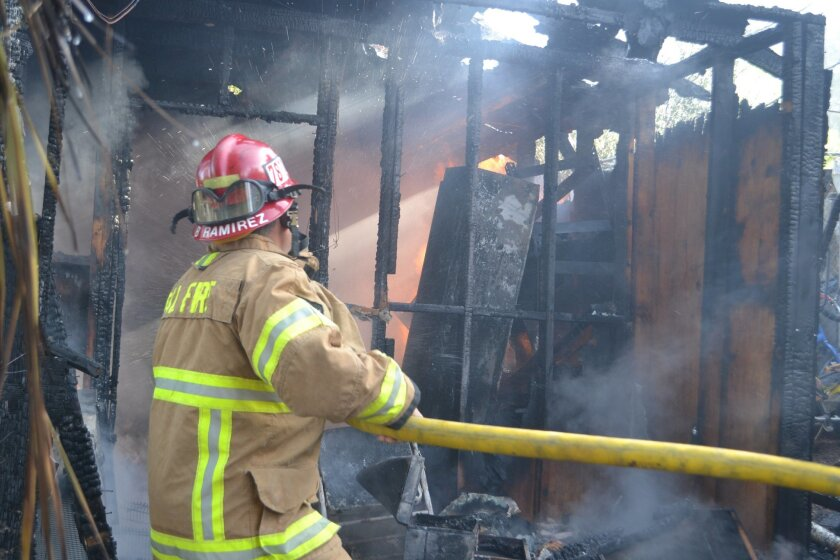 Ramona/Cal Fire Capt. Robert Ramirez extinguishes a flame in a shed that caught fire Thursday morning.