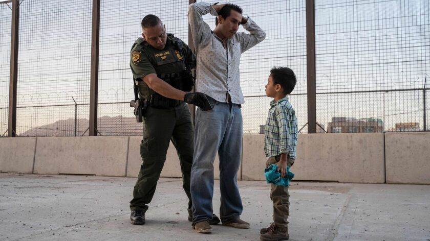 A Guatemalan man is searched by a Customs and Border Protection agent after he and his 7-year-old son crossed the border in El Paso on May 16.