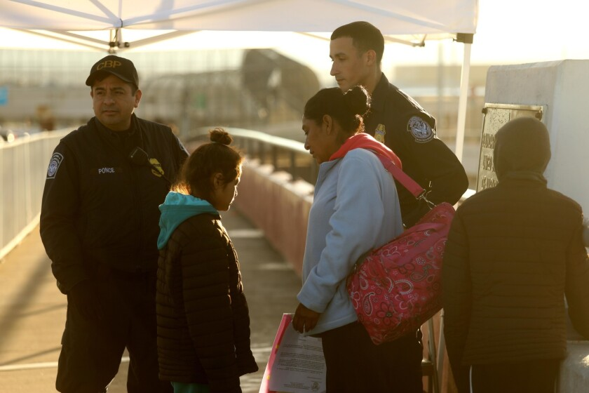 A Mexican mother, center, and her children are denied entry by border agents after requesting asylum in the U.S. on an international bridge in Ciudad Juarez, Mexico.