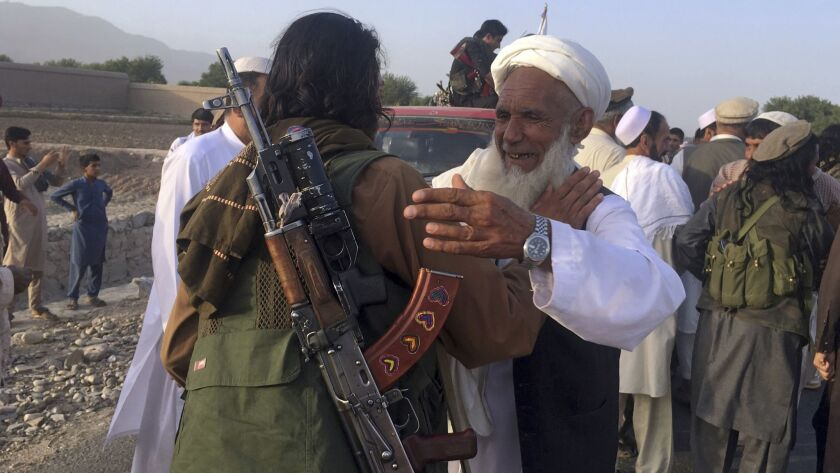 FILE - In this June 16, 2018 file photo, Taliban fighters gather with residents to celebrate a three