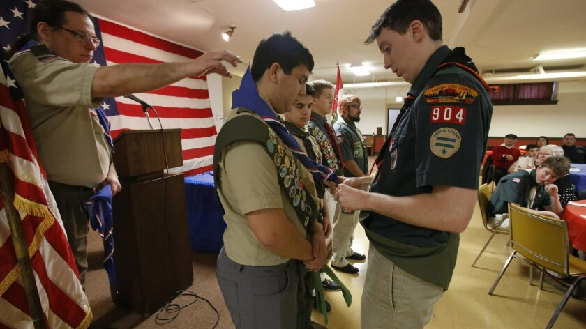 A fellow Eagle scout presents David Fite with his Eagle neckerchief during a ceremony at a Catholic church in Chicago on Sunday, Jan. 3, 2016, as Fite's scoutmaster, Jerome Lasky, stands behind him. To earn Eagle rank, David earned 21 merit badges and organized a two-part community service project