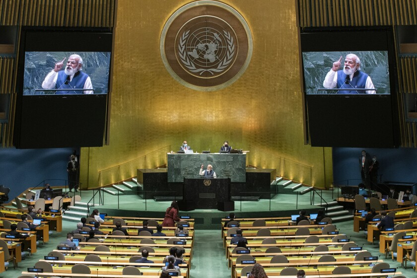 India's Prime Minister Narendra Modi addresses the U.N. General Assembly from a podium with large video screens above him