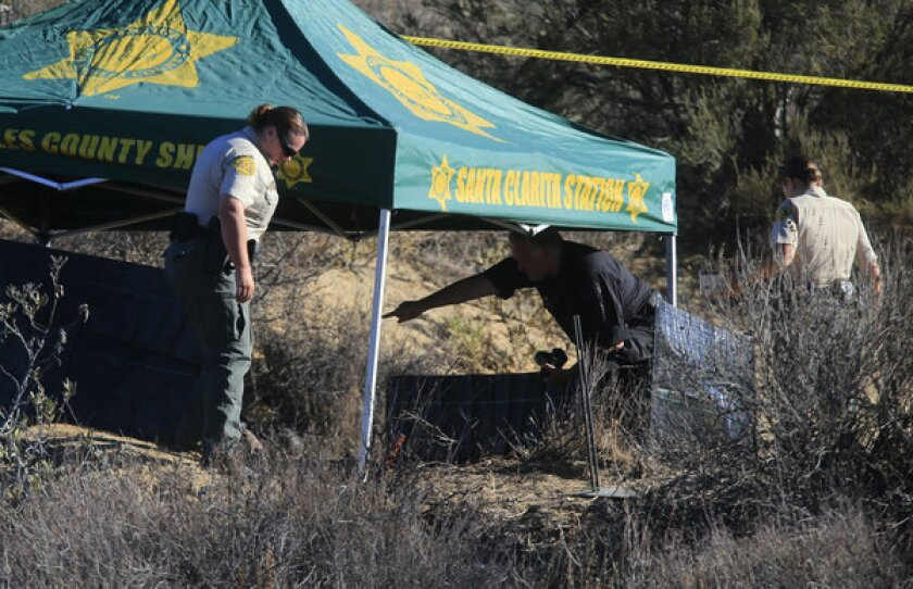 Investigators gather evidence off Lake Hughes Road in Castaic where a body was found burning early Wednesday morning.