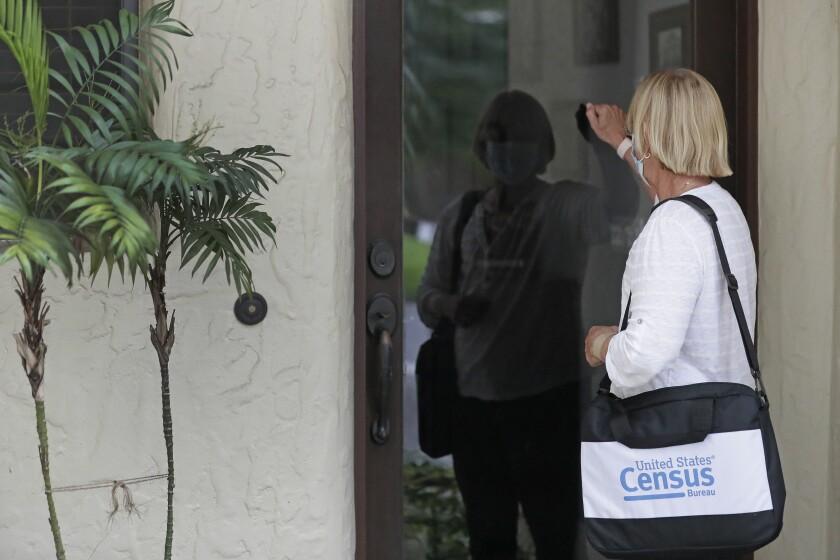 Fotografía de archivo del 11 de agosto de 2020 de una censista tocando la puerta de una residencia
