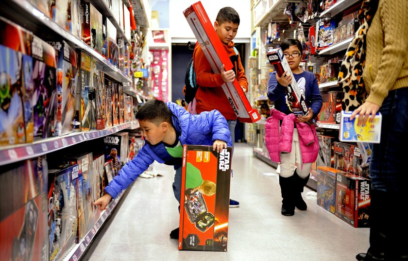 From left, Inaki, 7, Inigo, 13, and Bianca Casido, 9, shop at a Toys R Us store in Los Angeles with their mother Kristine, right, on Dec.14, 2015.