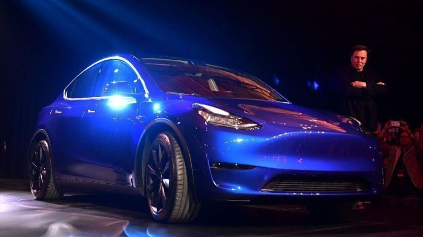 Tesla CEO Elon Musk displays the new Tesla Model Y at its unveiling in Hawthorne, Calif., on March 14, 2019. The all-electric SUV, which seats seven, is slated to start at $39,000 with the first versions rolling out in fall 2020.