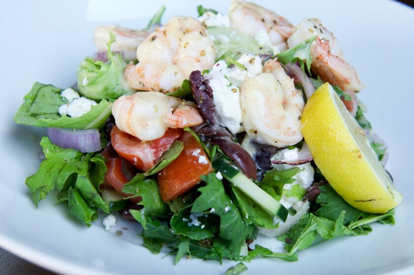 Athenian Greek salad topped with tiger shrimp.